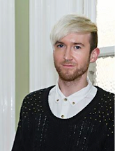Begin image. A young white man dressed in a white shirt and black knitted jumper is smiling at the camera. He is standing in front of a window. He has blonde hair and brown stubble. End image.