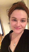 A 20 something white woman smiles gently to the camera in a well-lit kitchen. She is wearing a sparkly bronze headband with her shoulder length dark brown hair pulled up in a bun. She has a tiny white gem nose stud and an opal pendant necklace on and a purple velvet jacket which is zipped most of the way up.