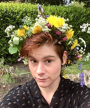 Begin image. Eren is white and in his twenties.  He is standing in front of a laurel hedge and is sporting a majestic wild flower crown.  He has hazel eyes and matching hair.  He has a small smile and slightly raised eyebrows. He is wearing a black shirt with small rainbow writing saying proud. End image.