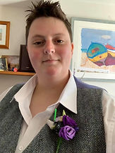 A mature white woman is smiling at the camera. She has short brown hair and is wearing a white button down shirt with a greay waistcoat. She has purple flowers pinned to her waistcoat. She appears in front of picture frames. End image.