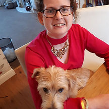Begin image. A young white women with short brown hair and black glasses is sat down, smiling at the camera. She is wearing a red long sleeve top with a low neckline and a chunky necklace. In her arms is a little dog. End image.