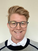 Begin image.  A headshot of a woman with blond hair which is short at the sides and longer on top & flops to the left. She is in front of a white background and facing directly forward with a slightly wonky smile, she is wearing glasses and you can just see the collar of her white shirt and navy and grey jumper. End image.