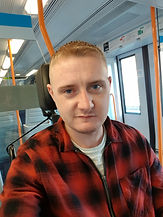 Begin image. A young, white man with short, blonde hair and blue eyes is facing the camera and smiling. Behind his head is the black headrest of his wheelchair. The background is the inside of a train carriage, with one orange metal pole behind him to the left, one behind his head, and one to the right. Double doors to the train carriage are also behind him to the right. He is wearing a red and black large checked, zip up shirt, zipped half way up with a beige t-shirt showing under the unzipped top of the shirt. End image.