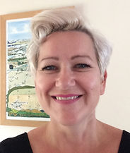 Begin image. This is a headshot of a mature white woman standing in the middle of the photograph facing directly towards the camera.  She is in a brightly lit room and in the background to the left is an abstract landscape painting. She has short blond hair, and has a friendly, bright smile which makes her nose crinkle. End image.