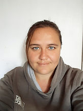 Begin image. A white women is smiling at the camera in front of a white backdrop. Her brown hair is tied back and she is wearing a grey hoodie. End image.