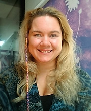 Begin image. Claire is a white British, blond, female presenting human who is smiling in the photo. She has slightly big blond hair with a thin multi coloured braid hanging on the left side of their head. They have green eyes and a large green woollen shrug wrapped round them with a black tank top underneath. End image.