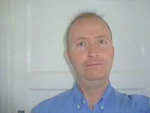Begin image. A friendly looking, white middle aged man, clean shaven with short dark hair, is standing just off-centre to the right of the picture. He is looking straight at the camera and he is wearing a bright blue shirt, unbuttoned at the neck, standing in front of a white background. End image.