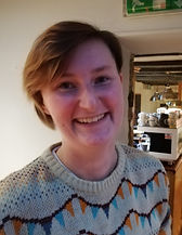 Begin image. A young white person with short brown hair is smiling at the camera. They are wearing a knitted jumper and appear to be in a cafe. End image.