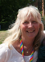 Begin image. A mature white women with long blonde hair is smiling at the camera. She is wearing a rainbow lanyard around her neck and sunglasses on top of her head. She is surrounded by grass and trees. End image.