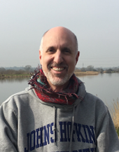 Begin image. A mature bald, white male with a grey beard, wearing a pullover sweatshirt with a brightly coloured scarf around his neck stands outside in front of a small lake.  There are trees in the distance on the far shore.   He is facing directly to the camera and smiling. End image.