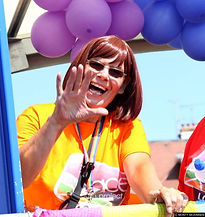 Begin image. A mature white women in an orange t-shirt with the SYP logo on the front. She is wearing a rainbow lanyard. She had short brown hair and is wearing sunglasses. She is surrounded by purple and blue ballons and she is smiling and waving at the camers. End image.