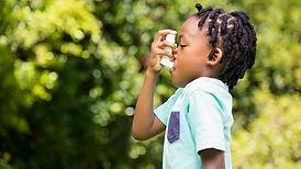 child using inhaler for allergy season.j