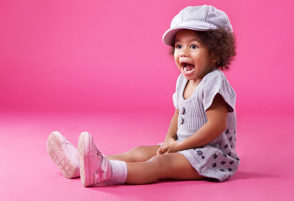Portrait of a little girl in stylish clothing sitting on pink background and playing up.jpg