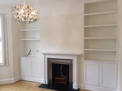Made-tomeasure cupboard and shelving system aside the chimney breast