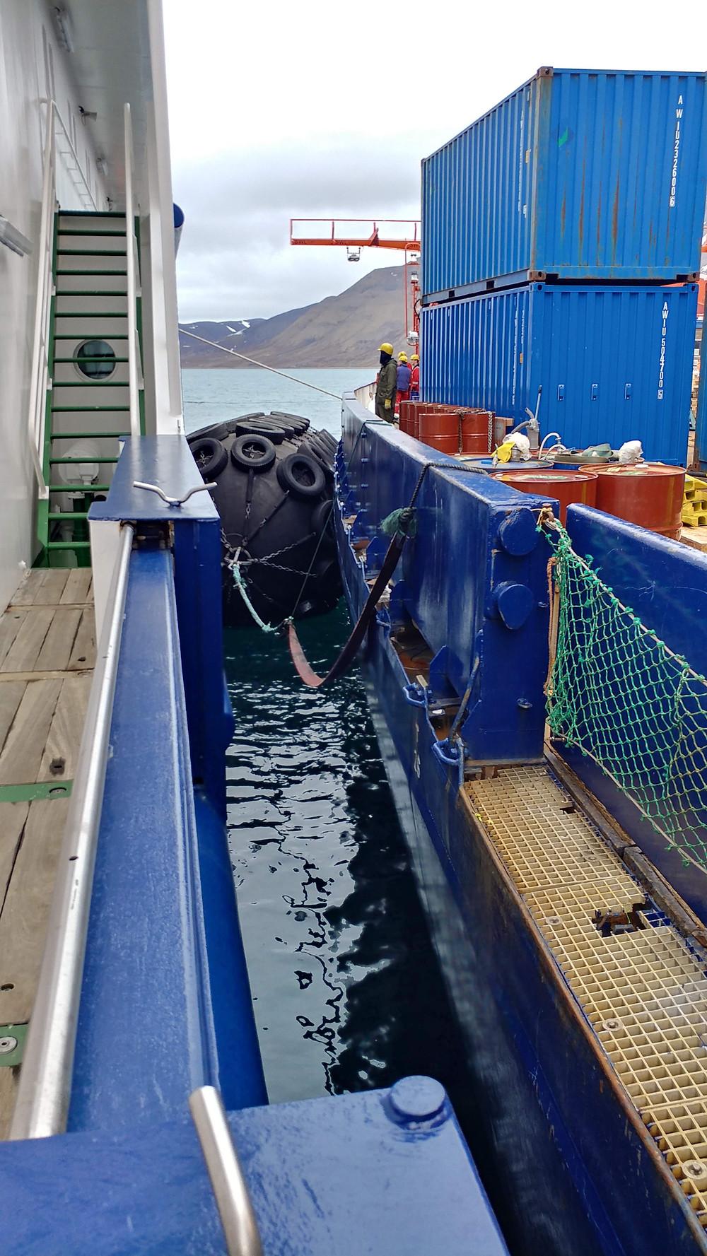 Fotografia de dois navios lado a lado no Ártico. Dois grandes contêineres azuis e vários barris laranja são vistos na embarcação à direita, com uma única pessoa ao fundo. Uma grande bóia com pneus protege os navios da colisão um com o outro. Ao longe, a água parece calma e há morros marrons.