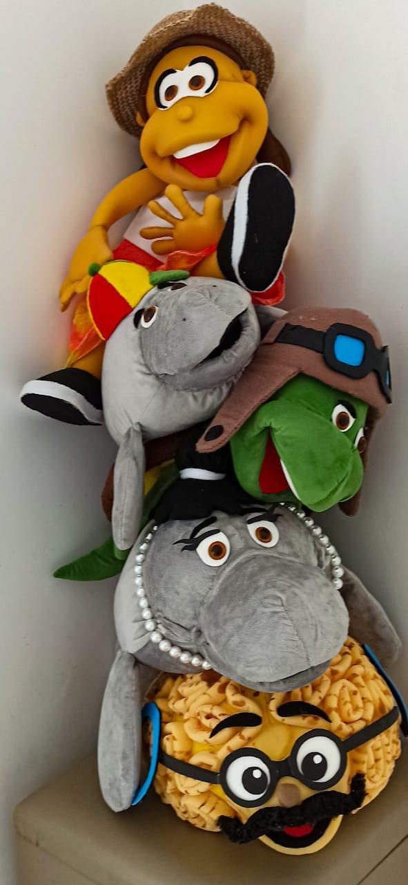 Fantoches dos personagens da série Mar a Vista. Observamos um coral cérebro amarelo com bigode e óculos que na série faz papel de professor. Depois vemos uma peixe boi fêmea cinza com colar de pérolas que é mãe de Tutu, um peixe boi criança que é o personagem principal da série. Tutu veste um chapéu vermelho e amarelo. Também observamos uma Tartatuga de chapéu e óculos e um humano com chapéu de palha de pescador.