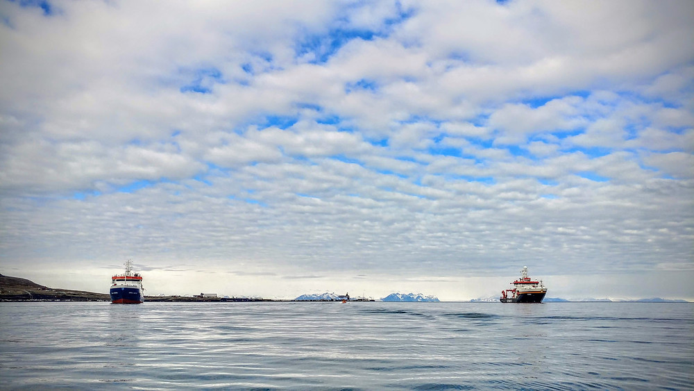 Photograph of an Arctic landscape. A blue sky with lots of white clouds takes up about two thirds of the frame. In the lower portion, to the left is the Maria S. Merian research vessel and to the right the Sonne research vessel. In the far background there are snow-capped mountains.