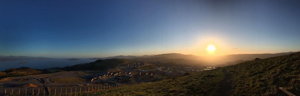 Foto tirada de cima de um morro bastante alto com vista para um pequeno bairro residencial nas montanhas, mar e um pôr do sol.