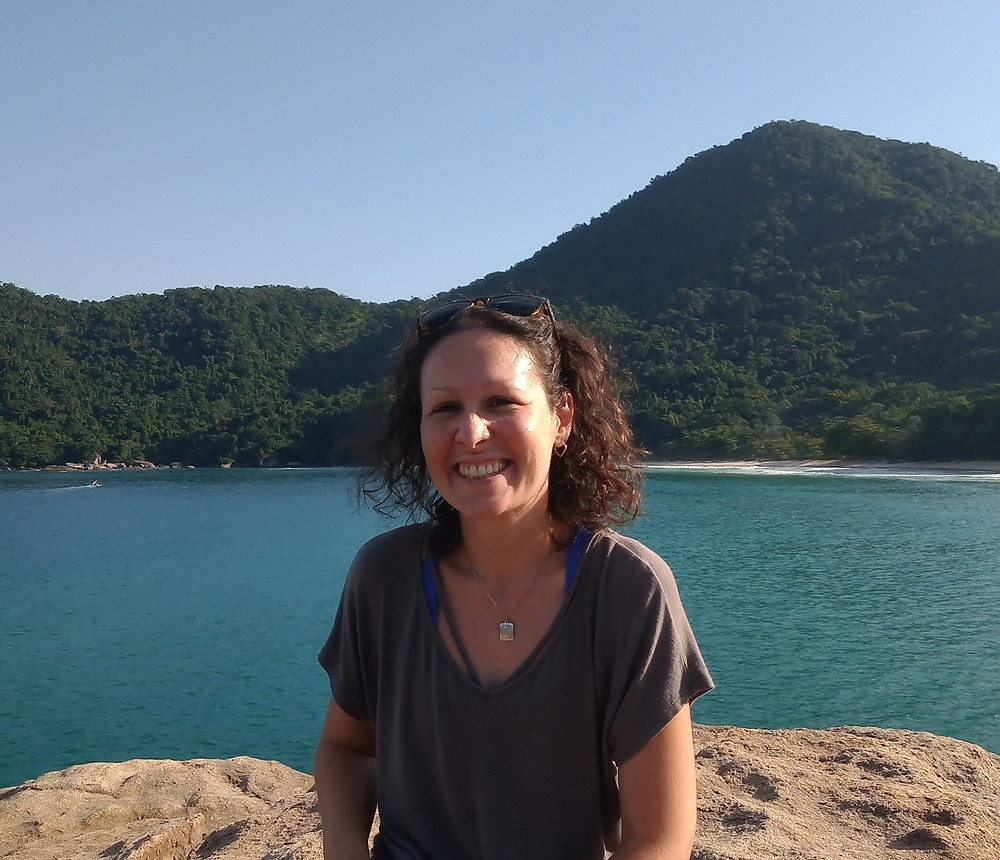 imagem da autora do texto, com montanhas e o mar azul ao fundo.