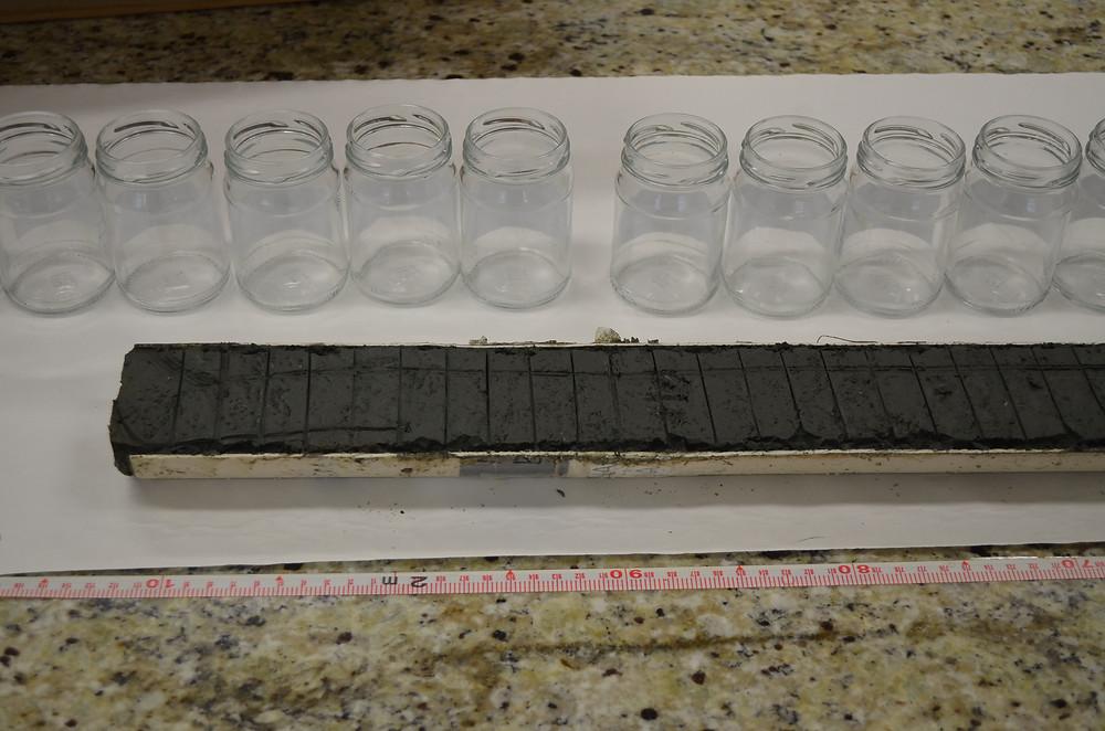 Exemplificacao de testemunhos. Cano de PVC com sedimento dentro cortado em diferentes fatias/tamanhos, de acordo com a profundidade e idade geologica.