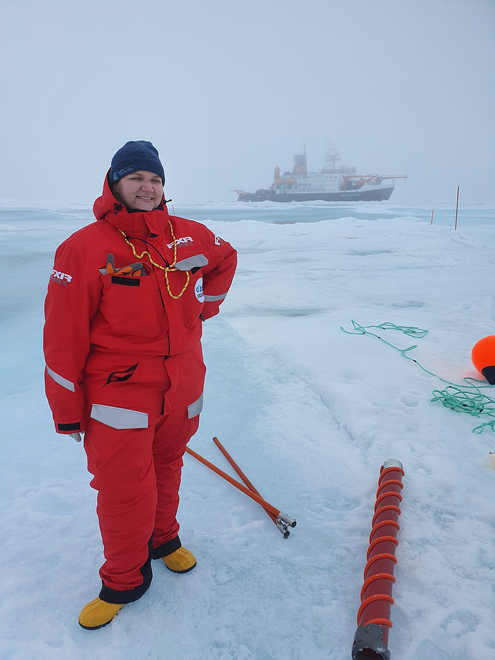 Female marine scientist smiles to the camera wearing a red jumpsuit, yellow rubber boots, and ice picks around her neck. She is standing on the ice in the Arctic Ocean with ice coring equipment around her and  a research vessel  in the background.