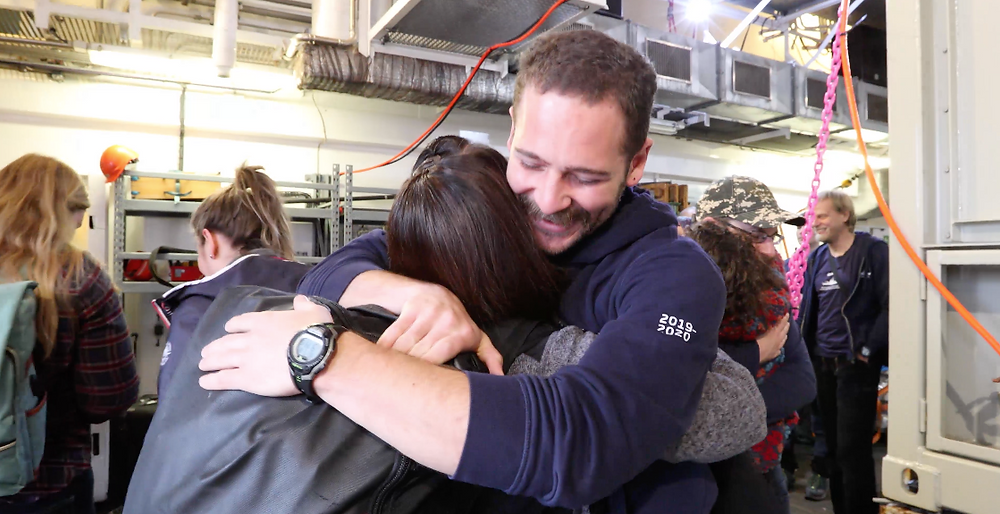 Two pairs of marine scientists embrace smiling while surrounded by other scientists. The people are wearing jackets and backpacks, and in the background there are shelves with protective equipment.