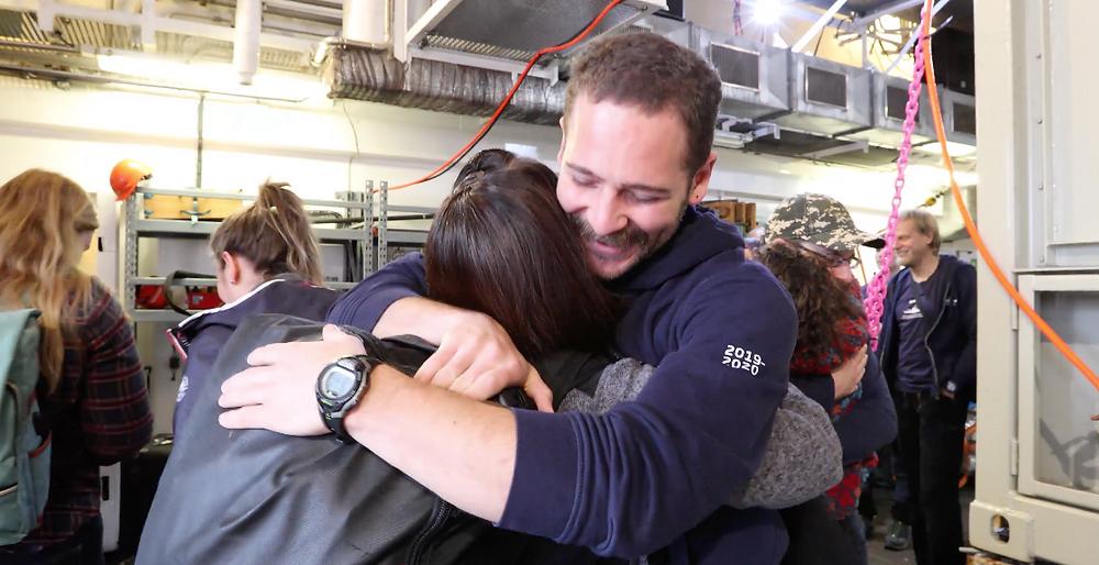 Duas duplas de cientistas marinhos se abraçam sorrindo enquanto estão rodeados por outros cientistas. As pessoas vestem jaquetas e mochilas e, ao fundo, estão as prateleiras com equipamentos de proteção.