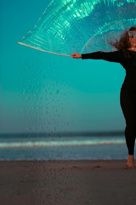 Fotografia de mulher dançando na praia. Ela veste uma roupa preta e tem em suas mãos um bastão com um pano brilhante. A mulher está no canto da foto, aparecendo apenas a metade do seu corpo. No fundo há ondas quebrando na praia