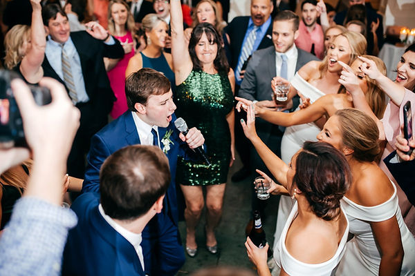 Groom sings in the mike with bride, wedding party and guests watching