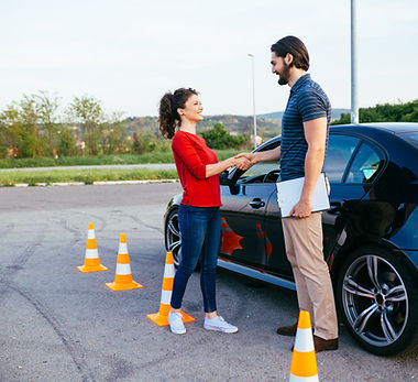 Driving school or test. Beautiful young woman with instructor learning how to drive and pa