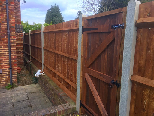 The back side of feather edge fencing, showing the frame work and arris rails.