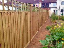 Light brown wood fence with trellis.