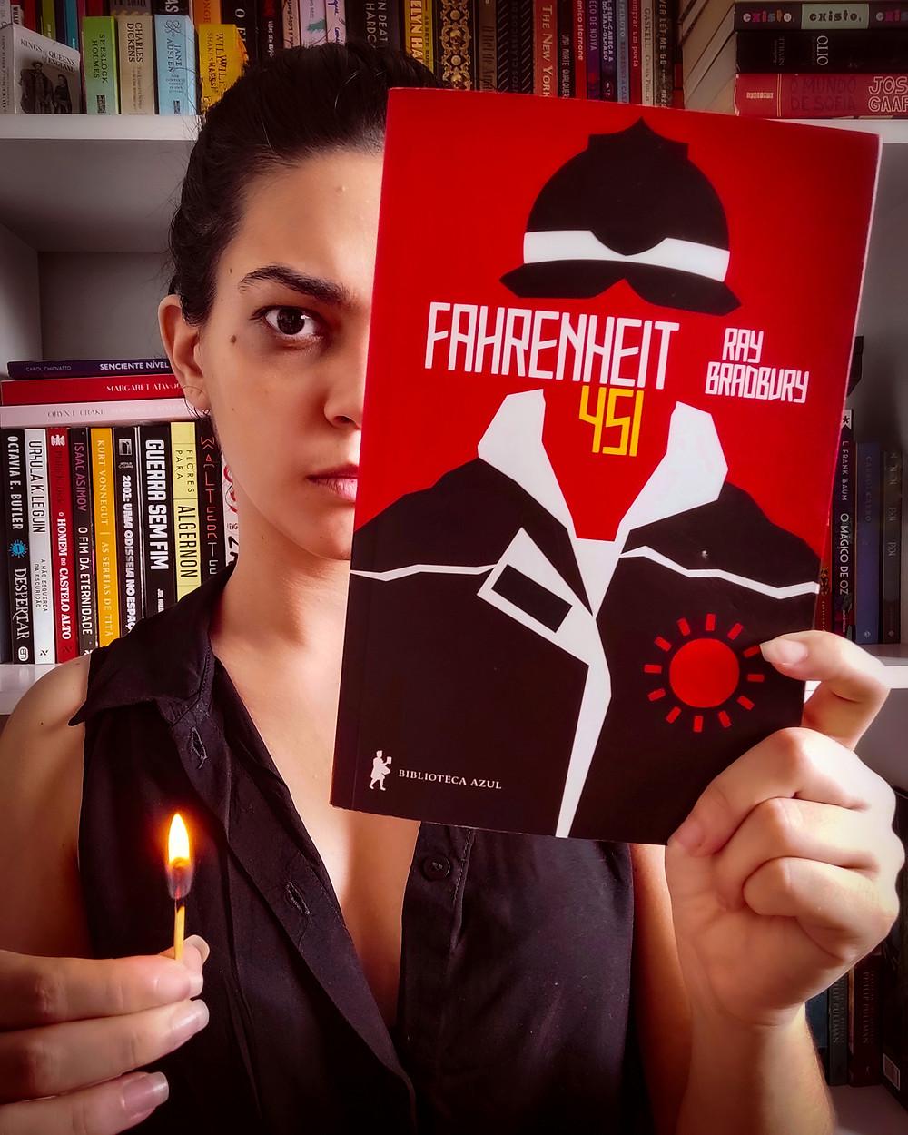Uma mulher segura o livro Fahrenheit 451 de Ray Bradbury e um fósforo aceso diante de uma estante de livros.