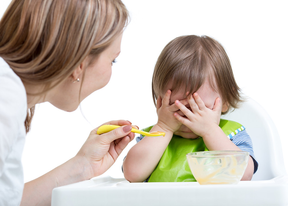 baby refusing spoon-fed purees from mother