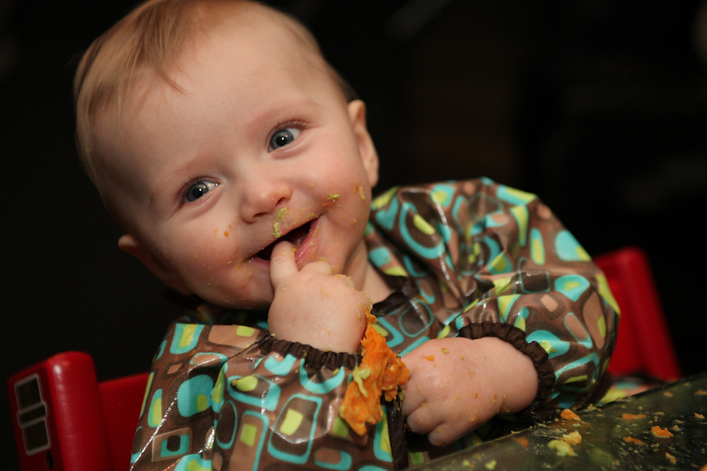 Happy baby led weaning baby with food on face