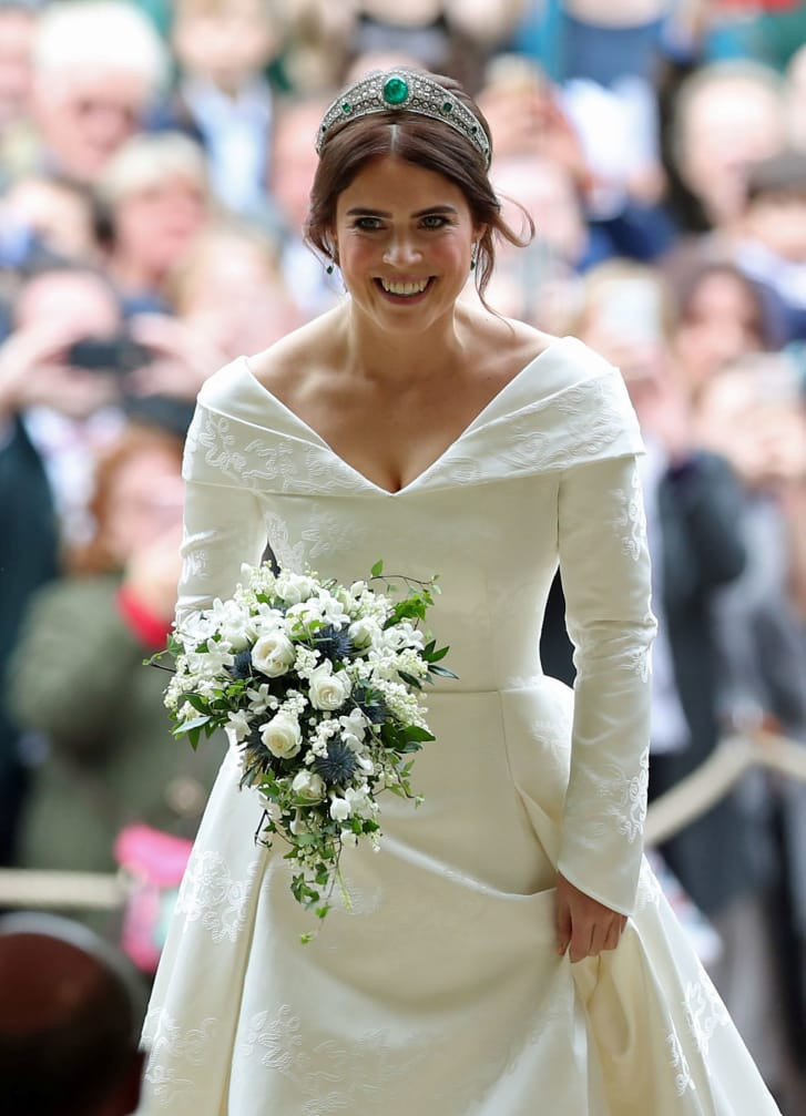 bride wearing white gown and carrying a blue a white floral bouquet