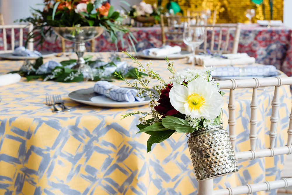 wedding table with yellow table cloth and flowers