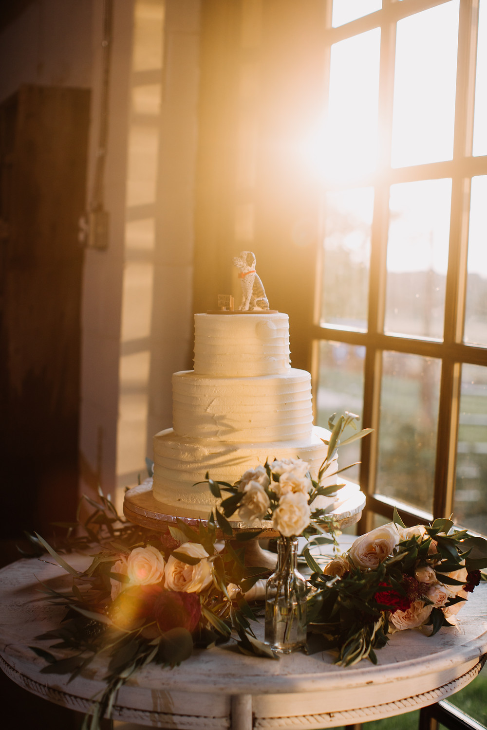 wedding cake decorated with flowers on table by a sunlight window