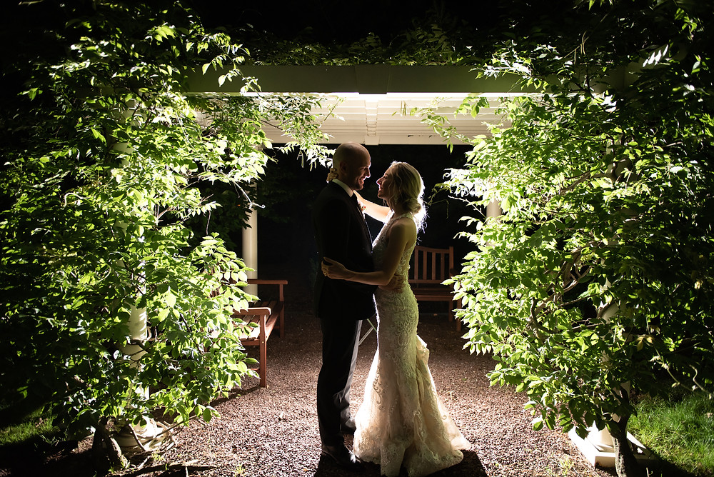 Bride and Groom dance in garden gazebo