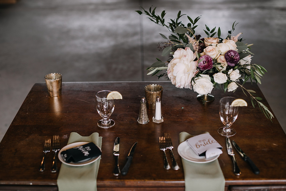 wooden table with glasses, cutlery and flowers