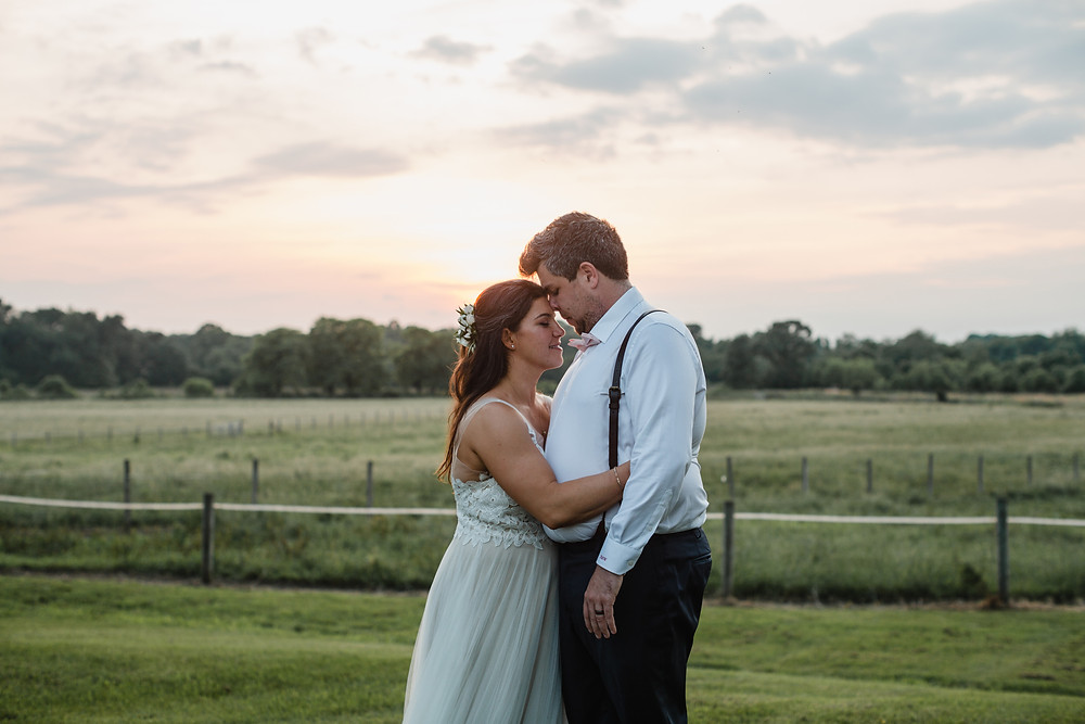 bride and groom embrace on farm at sunset