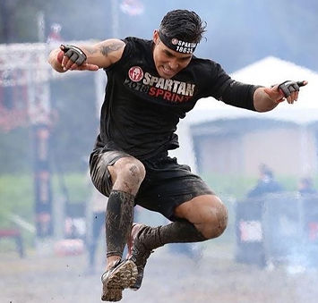 Spartan Coach Joe doing the finish line fire jump.