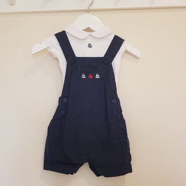 Up to one month. Navy romper and collared vest.