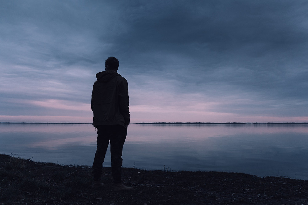 man standing on the shore looking at the water