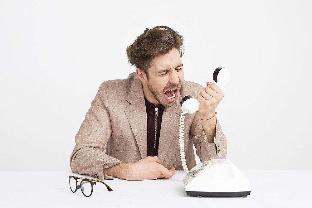 angry man shouting into telephone