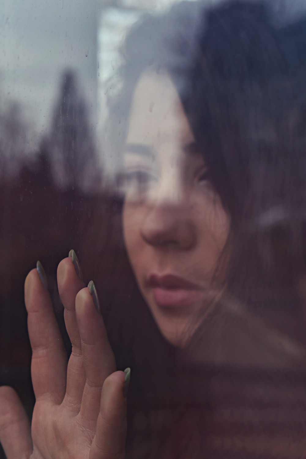 woman with hand on window looking out