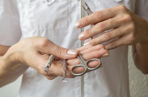 manicurista-sosteniendo-herramienta-cerc