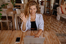 photo-of-woman-saying-hi-through-laptop-