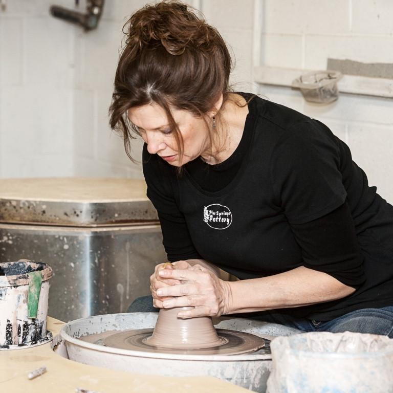 Woman potter working on wheel.