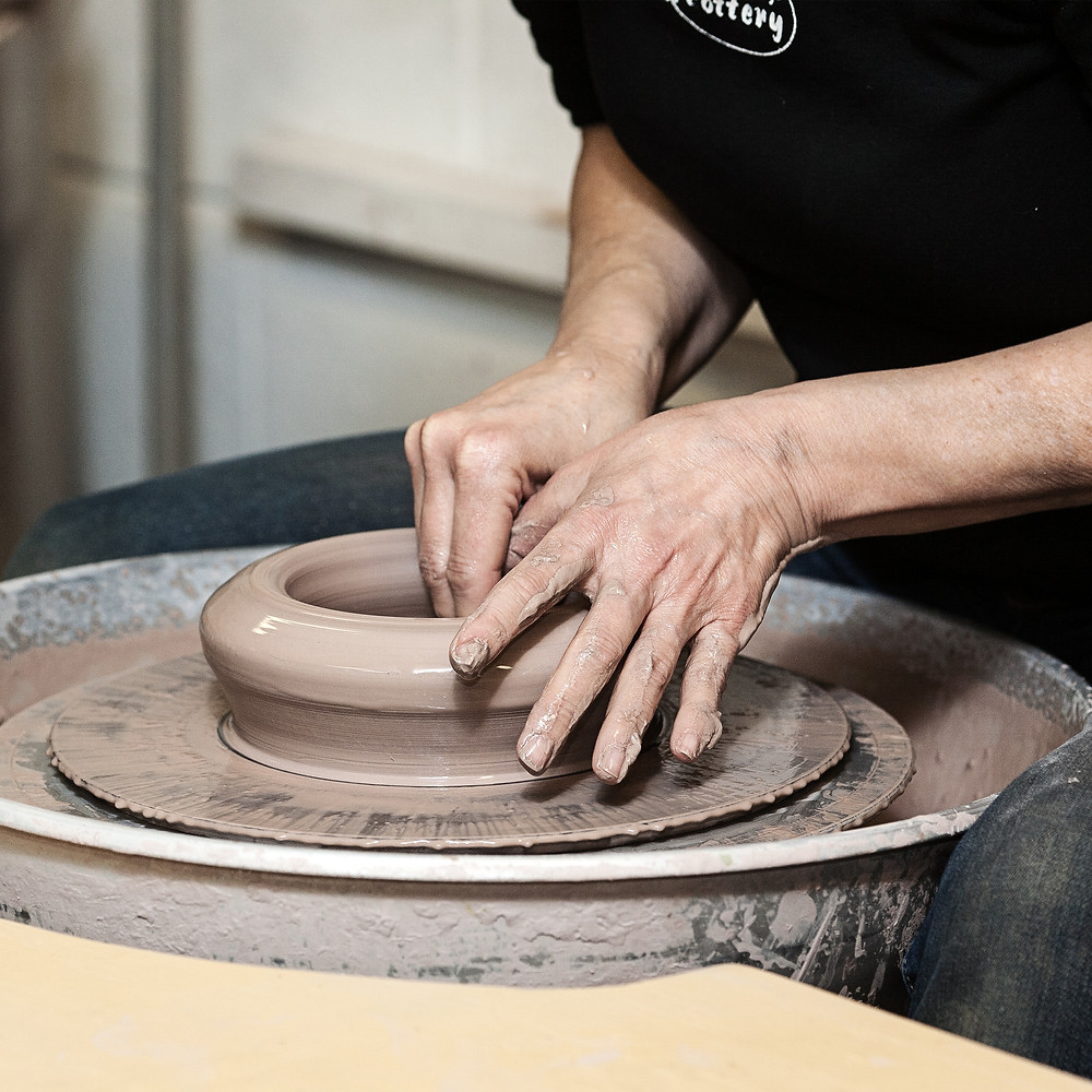 Hands working clay on potters wheel.
